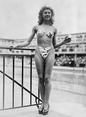Micheline Bernardini wearing the first bikini, 1946. The new 'Bikini' swimming costume (in a newsprint-patterned fabric), which caused a sensation at a beauty contest at the Molitor swimming pool in Paris. Designer Louis Reard was unable to find a 'respectable' model for his costume and the job of displaying it went to 19-year-old Micheline Bernardini, a nude dancer from the Casino de Paris. She is holding a small box into which the entire costume can be packed.